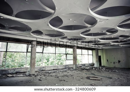 Abandoned industrial building interior. Empty hall with round pattern on ceiling - stock photo