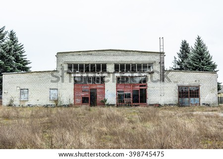 Abandoned industry, old industrial factory wall of white bricks with damaged door and windows - stock photo