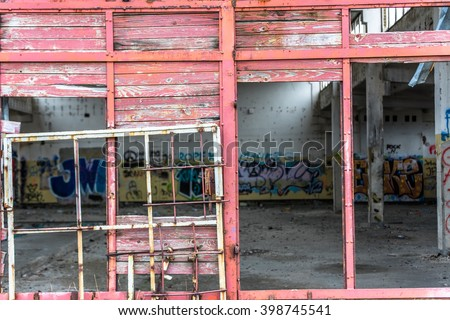 Abandoned industry, old industrial factory wall with damaged door - stock photo