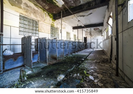 Abandoned interior of feeding room for cows with and great mess around on the floor. Creative composition photography by using wide angel lens. - stock photo