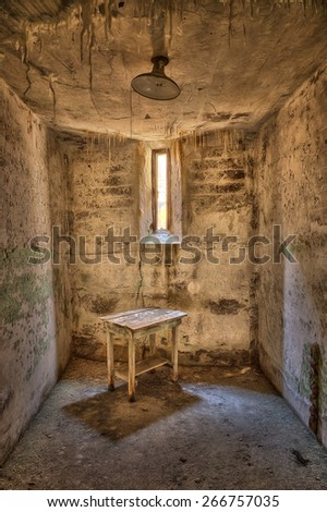 Abandoned Jail Cell with Table - stock photo