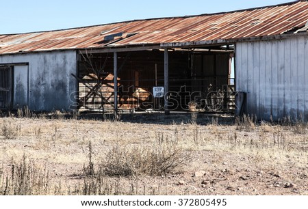 Abandoned long worn metal and wood empty barn with Keep Out sign/KEEP OUT Sign on Wooden Pole in Long Open Disused Weathered Corrugated Metal Building in Dry Rural Area/Keep Out of old abandoned shed - stock photo