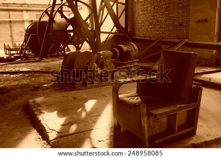 abandoned mechanical equipment and old sofa in a factory