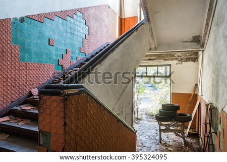 Abandoned messy staircase with broken red clay wall tiles in old factory interior - stock photo