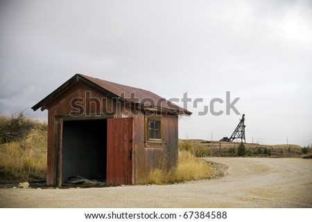 Abandoned Mine Storage Shed with Mine Head-frame in Background - stock photo