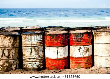 Abandoned oil barrels on the beachfront - stock photo