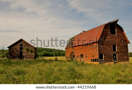 Abandoned old barns surrounded by beautiful blue sky.  Decaying wooden structures show weathering from desertion. - stock photo