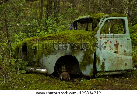 Abandoned old car covered in moss in the forest - stock photo