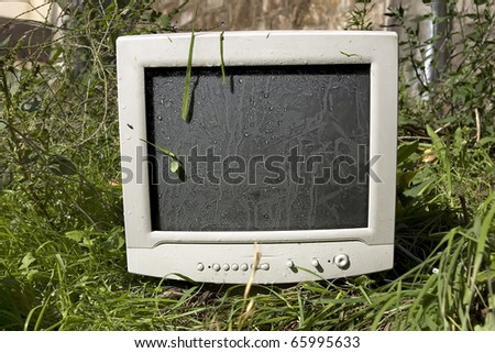 Abandoned old computer monitor in a public place.Concept of negligence. - stock photo