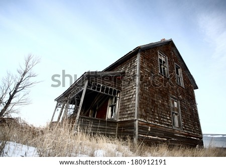 Abandoned old farm house in winter - stock photo