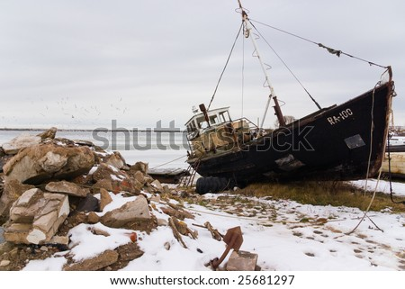 Abandoned old fishery boat and flying gulls - stock photo