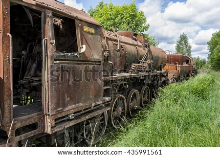 Abandoned old locomotive with cars