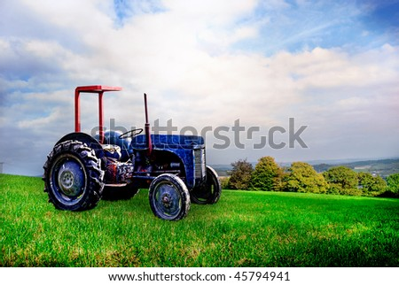 Abandoned old tractor in empty field. - stock photo