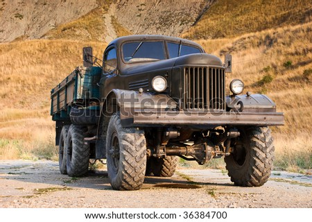 Abandoned old truck standing alone near the hill - stock photo