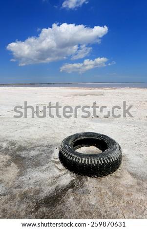 Abandoned old tyre on salt sea shore - stock photo