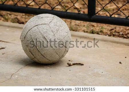 abandoned old volleyball on concrete floor in front of iron fence