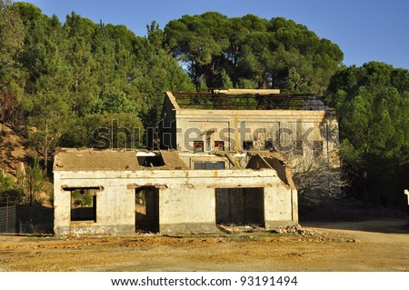 abandoned, old warehouse, machine shop or factory Sun shines through broken windows Large Pollution in Andalusia Spain - stock photo