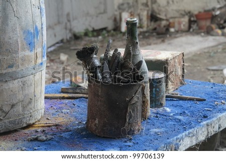 abandoned paintbrushes amidst dried blue paint pigment - stock photo