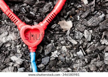 Abandoned plastic toy stethoscope on burned ground - stock photo
