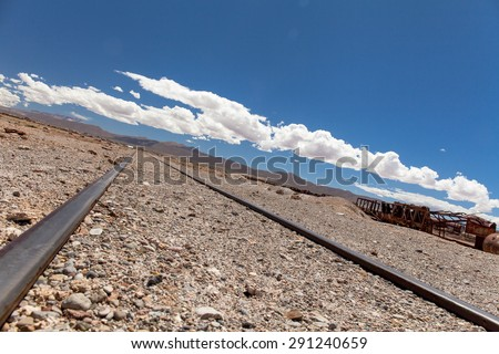 Abandoned railroad run to the horizon lines. Blue sky background with white clouds - stock photo