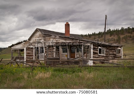 Abandoned ranch house built of logs and wood surrounded by a log fence on a rainy day