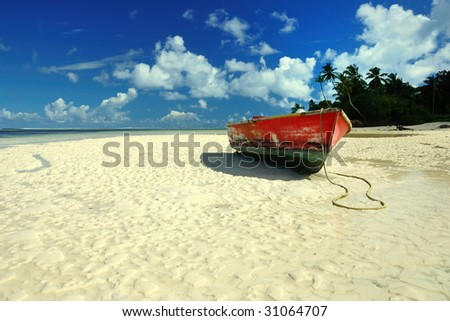 Abandoned red boat ion the beach - stock photo