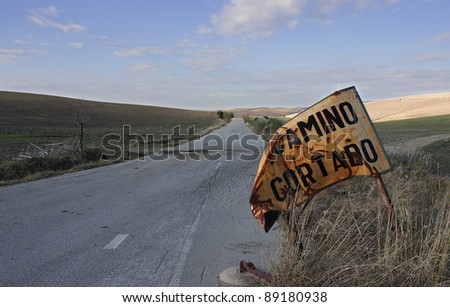 Abandoned road on the route of the white villages of Andalucia in which appears a sign indicating the road is cut.