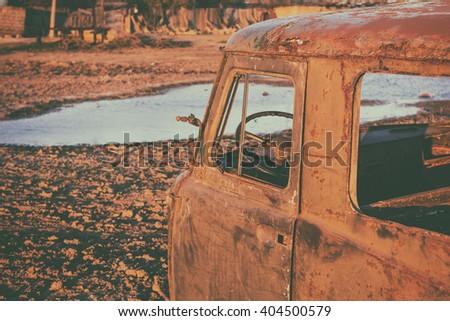 Abandoned rusty car. Retro style toned photo - stock photo