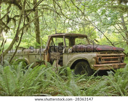 abandoned rusty truck with humorous sign - stock photo