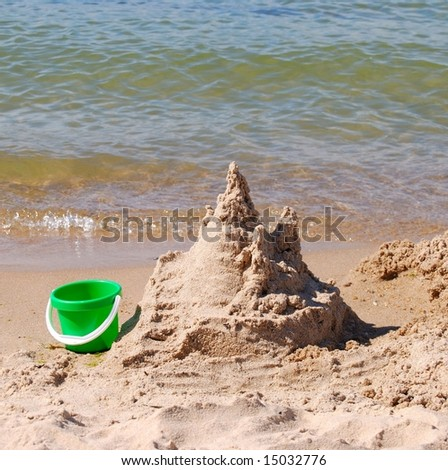 Abandoned sand castle and bucket at the side of a lake - stock photo