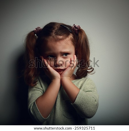 Abandoned scared kid with hands near face looking with horror on dark background. Closeup color portrait - stock photo