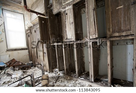 Abandoned school in Detroit Michigan. The cabinets are falling apart and papers are scattered on the floor. - stock photo