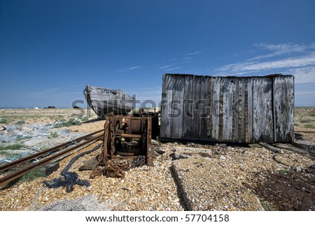 Abandoned seaside place with old boat wreck, fisherman house, service rails shot in sunny day with a blue sky - stock photo