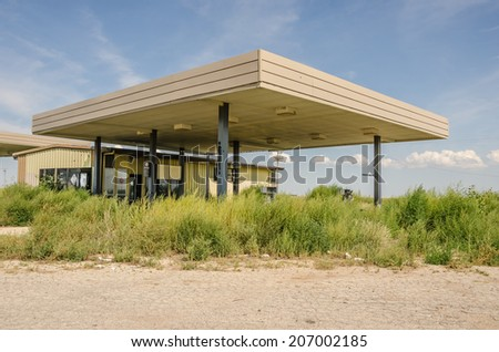 Abandoned service station on Route 66 with gas pumps destroyed and buried in the overgrown weeds - stock photo