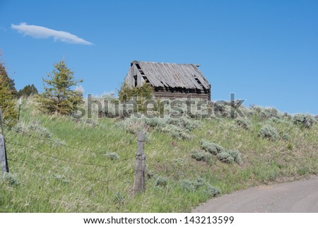 Abandoned shack beside a rural road in Gallatin County, Montana. - stock photo