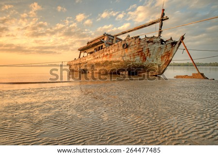 Abandoned Ship during sunrise moment at sabah borneo malaysia Image has grain or blurry or noise and soft focus when view at full resolution.  (Shallow DOF, slight motion blur) - stock photo