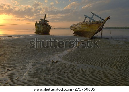 Abandoned Ship during sunrise moment at Sabah Borneo Malaysia.  Image has grain or blurry or noise and soft focus when view at full resolution. (Shallow DOF, slight motion blur)