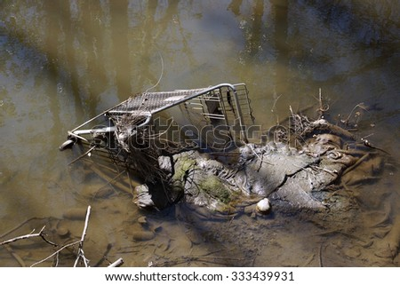 Abandoned shopping trolley in muddy water with other junk. - stock photo