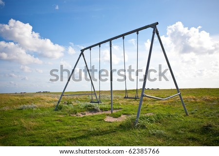 abandoned swing on a field on a sunny day - stock photo