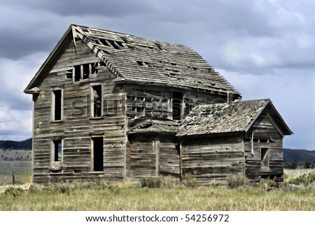 Abandoned 19th century house in a rural field in western America - stock photo