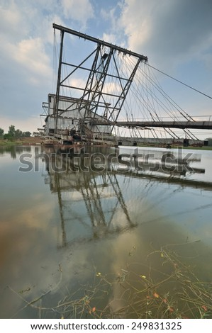 Abandoned tin mining dredge at Tanjung Tualang, Perak, Malaysia. Vertical View. - stock photo