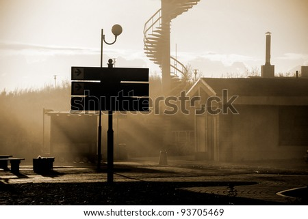 abandoned town street with mist and sunbeams at the sunset. Shallow depth of field - stock photo