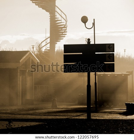 abandoned town street with mist and sunrays at the sunset - stock photo