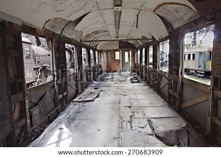 Abandoned train carriage with interior falling apart - stock photo