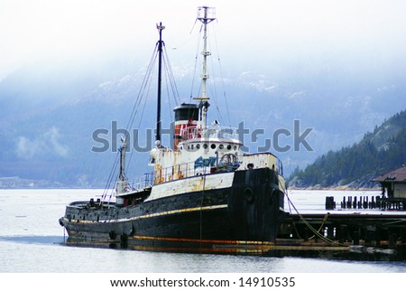 Abandoned tug boat in a misty bay amidst blue mountains