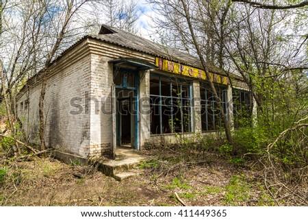 "Abandoned village in Chernobyl, Ukraine in a summer day. Sign in ukrainian ""Supermarket"" - stock photo"