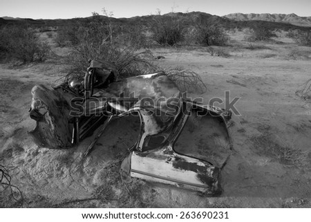 Abandoned vintage auto in the desert, landscape in black and white, Joshua Tree National Park - stock photo