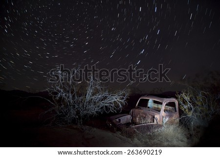Abandoned vintage auto in the desert, under star trails, Joshua Tree National Park - stock photo