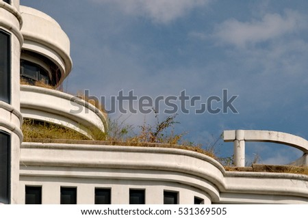 Abandoned white building with dry grasses on the balcony.