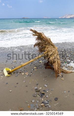 Abandoned wooden beach parasol on a wild beach. Crete, Greece 2013. - stock photo